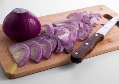 Red onion sliced on a blackboard